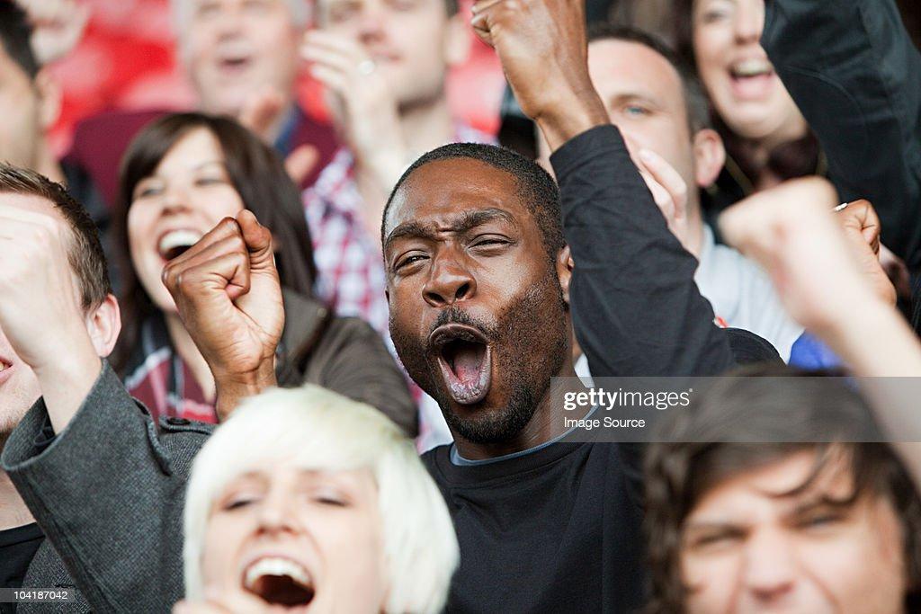 Cheering man at football match : Stock Photo