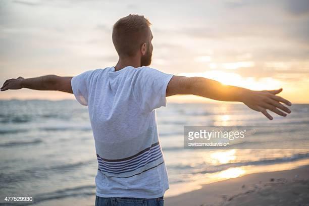 Acclamations homme bras ouverts au coucher du soleil à bord de mer