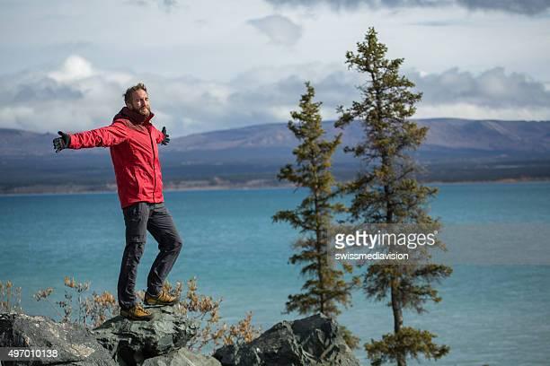 Acclamations homme debout sur une falaise, les bras tendus