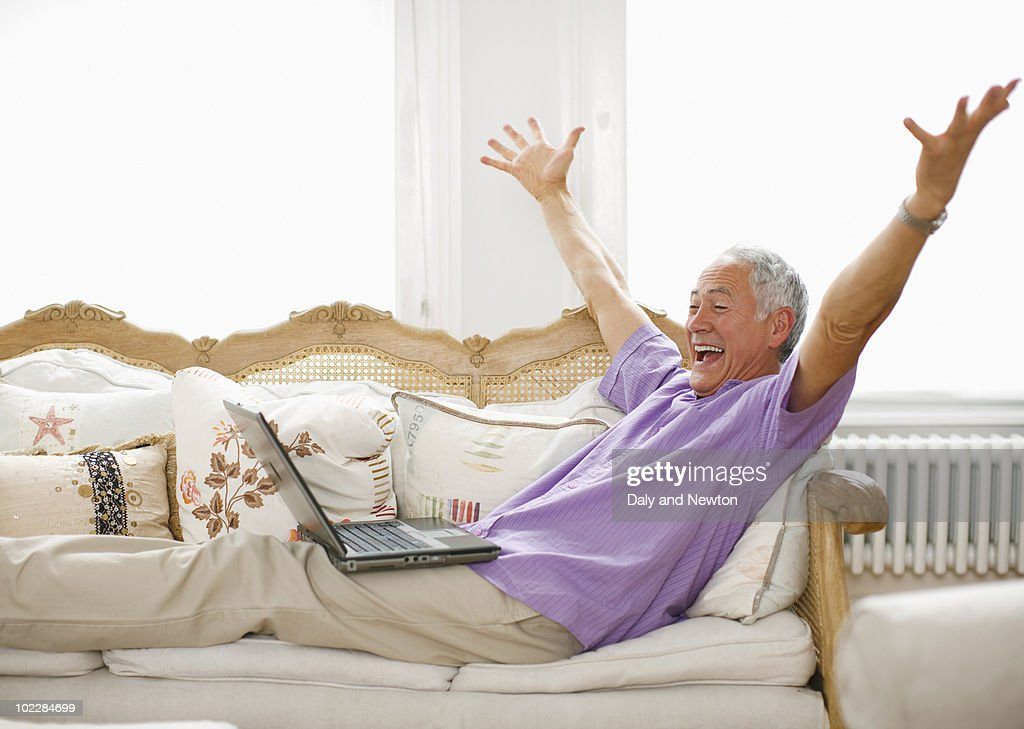 Cheering man using laptop : Stock Photo