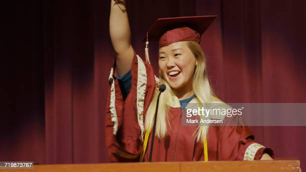 Cheering student speaking at podium on stage during graduation ceremony