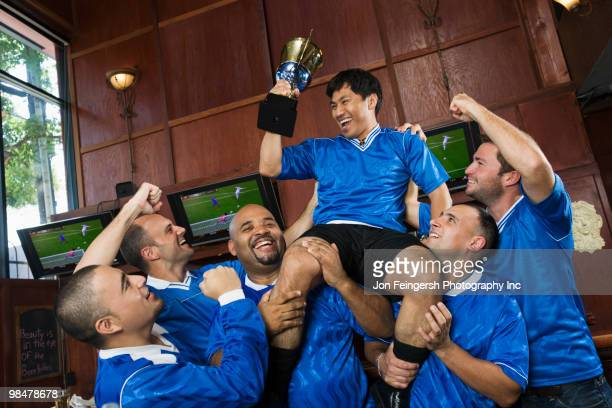 Cheering teammates lifting man holding trophy