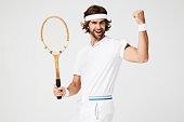 Cheering tennis dude with racket, portrait