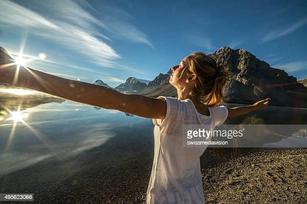 喜び女性の自然の湖の腕を広げる栄華