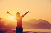 cheering woman open arms to sunrise at seaside