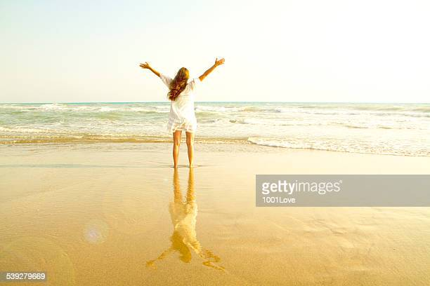 cheering woman open arms under sunrise on beach