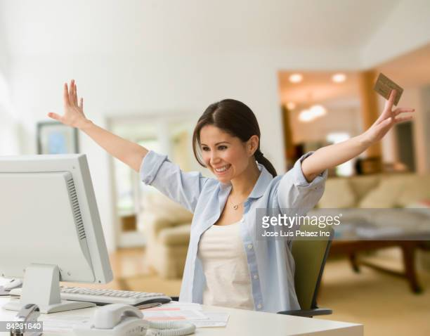 Cheering woman shopping online with credit card