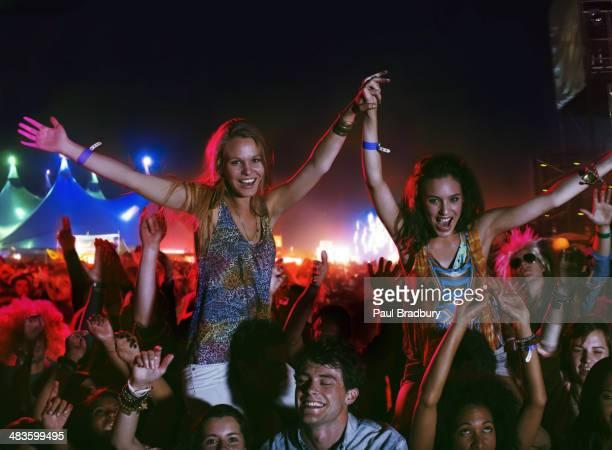Cheering women on menês shoulders at music festival