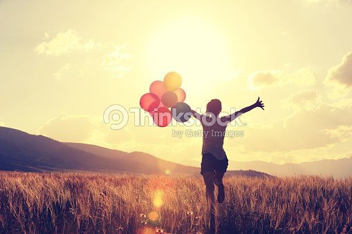 cheering young asian woman on grassland with colored balloons : Foto de stock