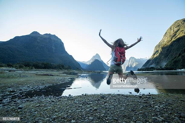 Cheering young woman jumps at Mitre peak-Milford sound, NZ