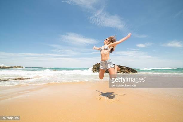 Jubeln junge Frau springt hoch am Strand
