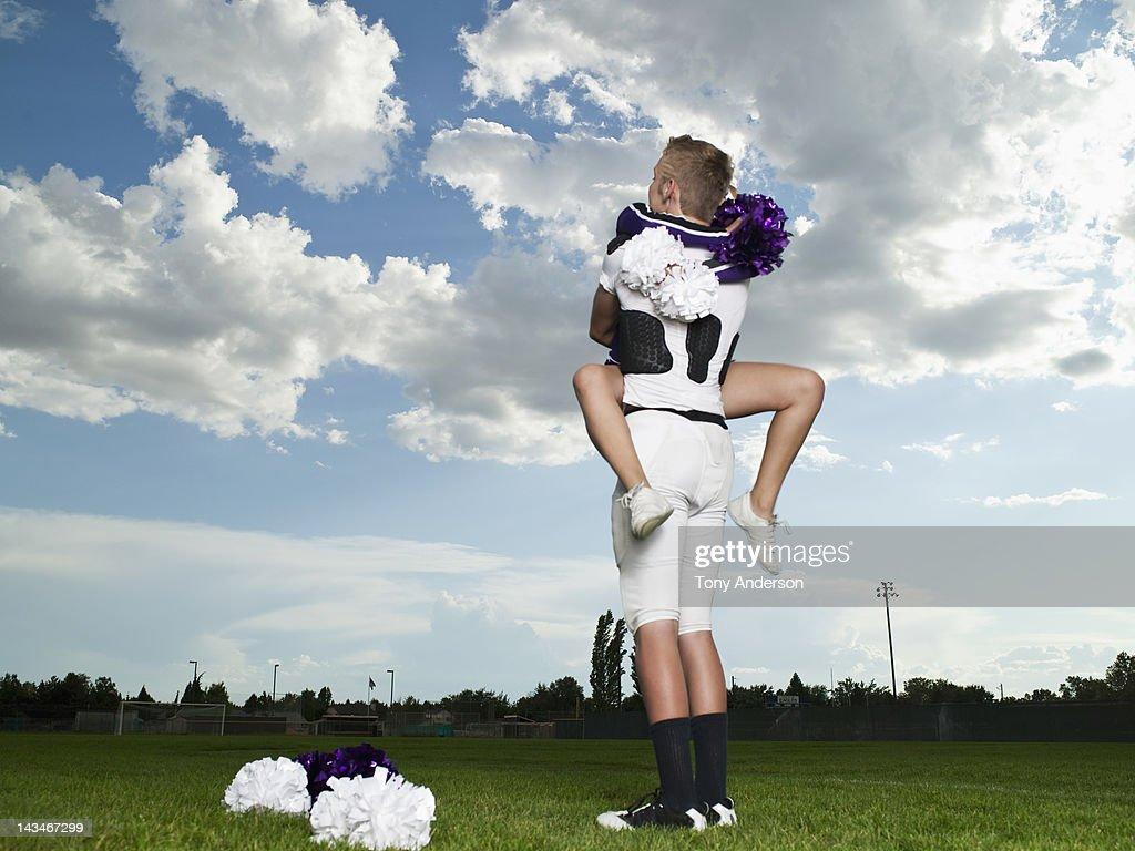 Cheerleader and Footballer Hugging : Stock Photo