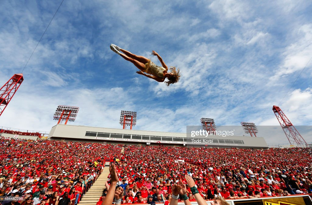 A cheerleader for the Edmonton Eskimos goes flying through the air while they played the Calgary Stampeders during their CFL football game September 1, 2014 at McMahon Stadium in Calgary, Alberta, Canada.