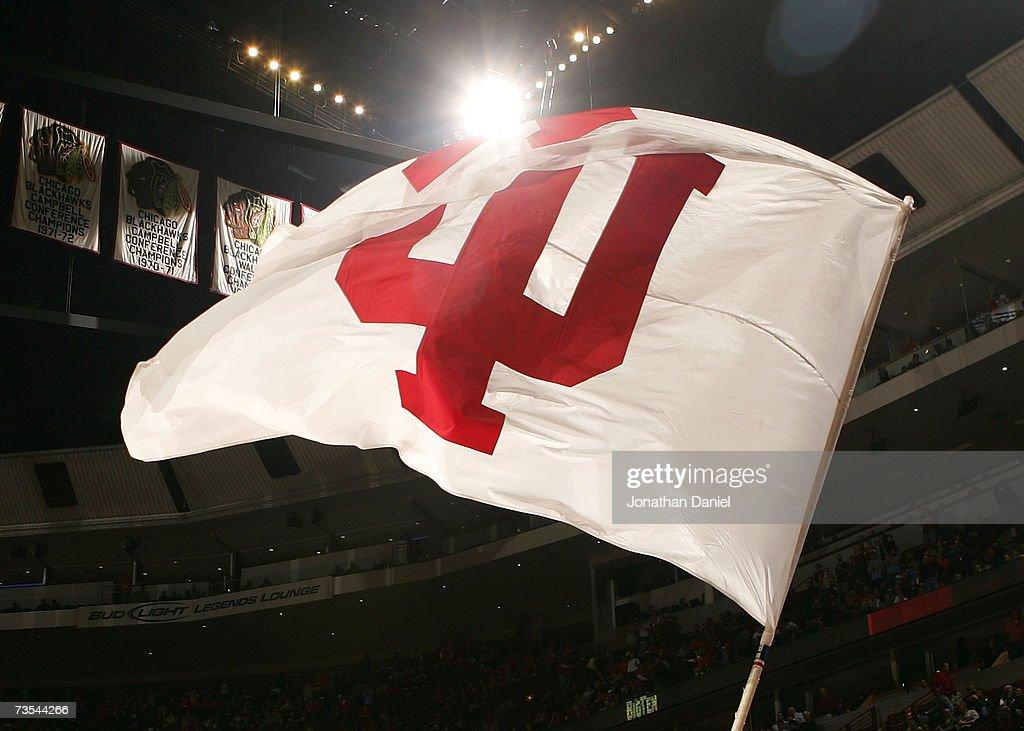 A cheerleader from the Indiana Hoosiers waves a flag with Indiana's logo on the court against the Illinois Fighting Illini during the quarterfinals...