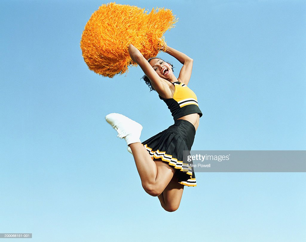 Cheerleader jumping in mid air, holding pompoms, portrait