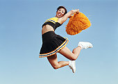 Cheerleader jumping in mid air, holding pompoms , portrait