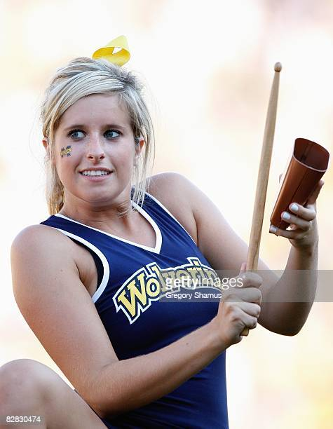 A cheerleader of the Michigan Wolverines plays the cowbell during the game against the Utah Utes on August 30 2008 at Michigan Stadium in Ann Arbor...