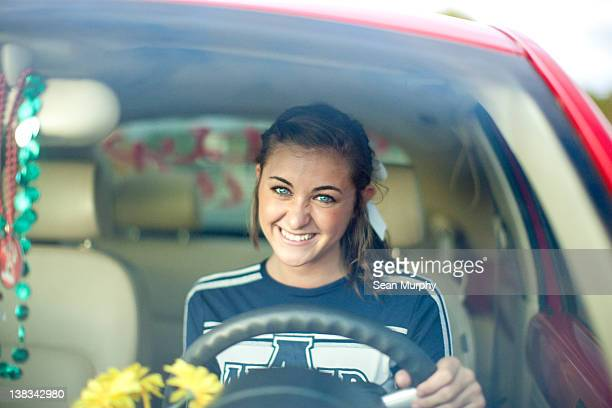 Cheerleader Smiles from Behind the Wheel