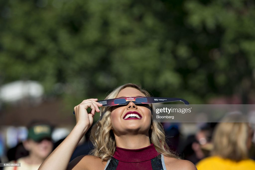 A cheerleader tests out a pair of solar viewing glasses during a eclipse viewing event on the campus of Southern Illinois University (SIU) in Carbondale, Illinois, U.S., on Monday, Aug. 21, 2017. Millions of Americans across a 70-mile-wide (113-kilometer) corridor from Oregon to South Carolina will see the sky darken as the sun disappears from view, albeit for only a few minutes at a time. Photographer: Daniel Acker/Bloomberg via Getty Images