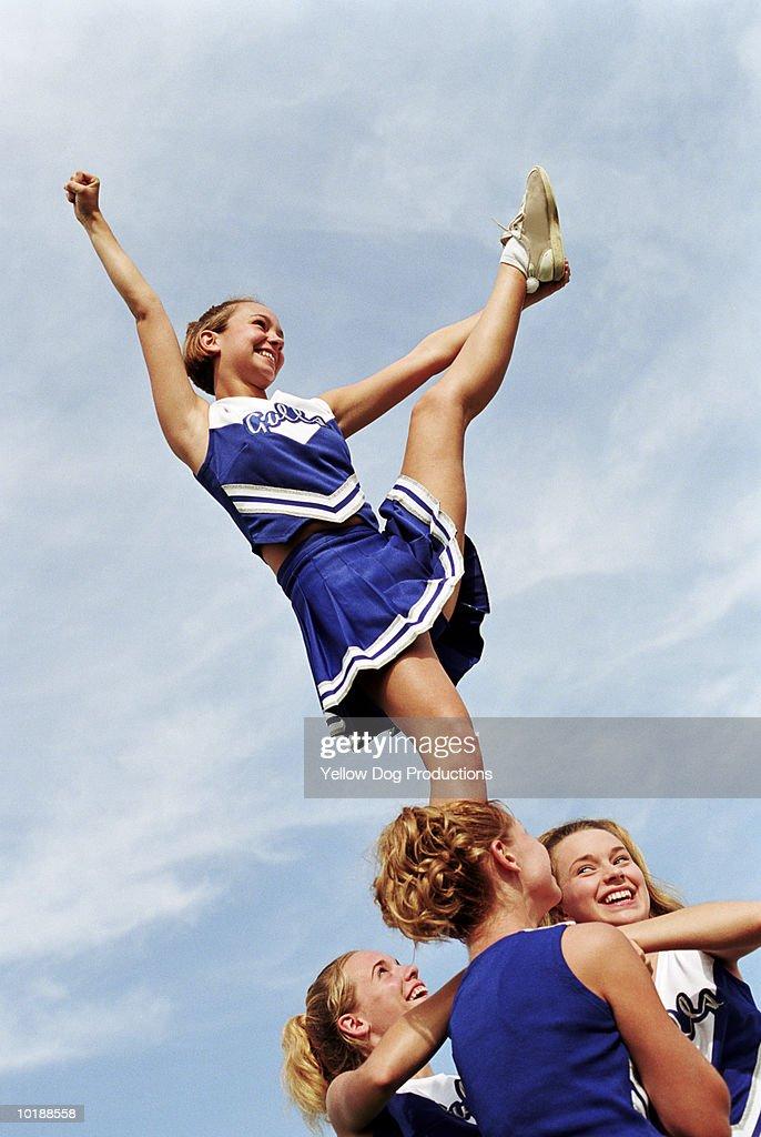 Cheerleader with leg raised on pyramid : Stock Photo