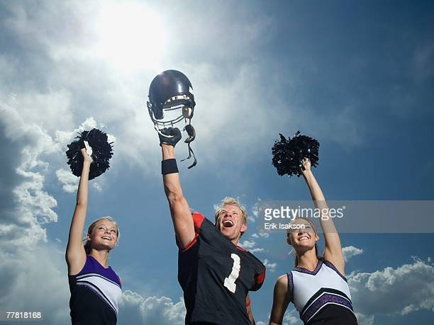 Cheerleaders and football player cheering
