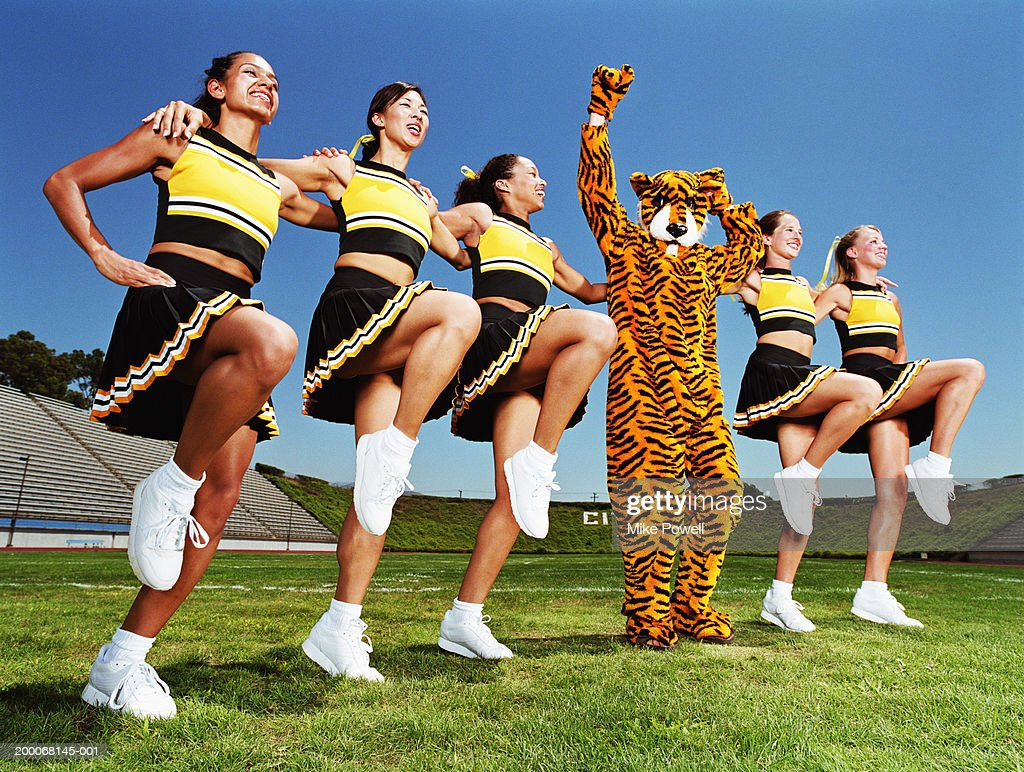 Cheerleaders dancing arm and arm in formation, tiger mascot in middle : Stock Photo