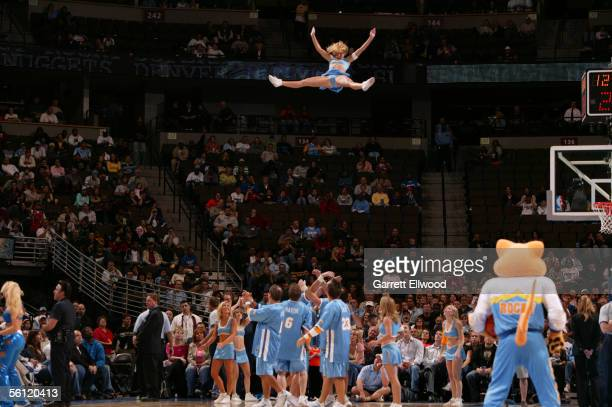 Cheerleaders from the Denver Nuggets perform a stunt during a stop in play against the Milwaukee Bucks during a preseason game October 26 2005 at the...