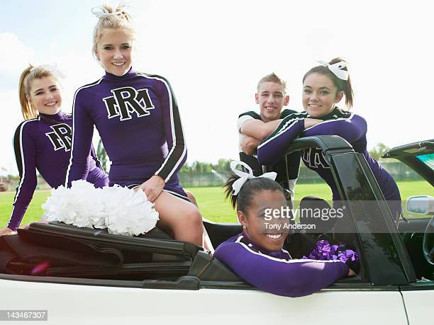 Cheerleaders Gathered around Car