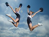 Cheerleaders with pom poms jumping