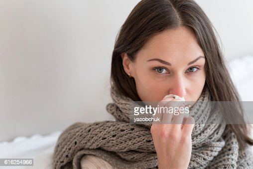 Cheerless ill woman using a paper tissue : Stock Photo