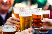 Close up color image depicting a group of people celebrating with a toast. The people cheers their glasses of beer (pints of beer) together in a gesture of celebration, togetherness and happiness. The