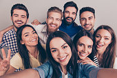 Cheers! Funky mood. Close up of an eight excited friend`s selfie, taken by brunette girl. Young people enjoy their company, smile, have fun