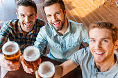 Top view of three happy young men in casual wear toasting with beer while sitting in bar together