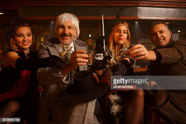 Cheers Retro pub celebration  Senior men and young woman drinking