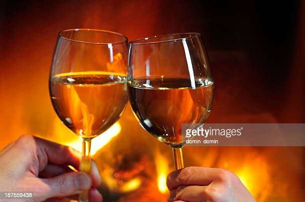 Cheers! Romantic date, close-up of wine against the fireplace