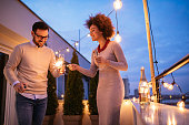 Photo of a young couple celebrating with sparklers on the terrace.