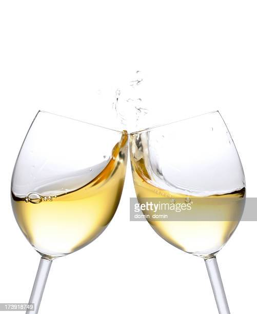 Cheers! Two white wine glasses with splash, isolated on white
