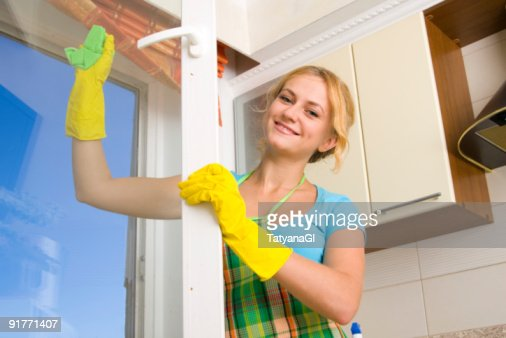 A cheery woman in yellow rubber gloves cleaning a window : Stock Photo