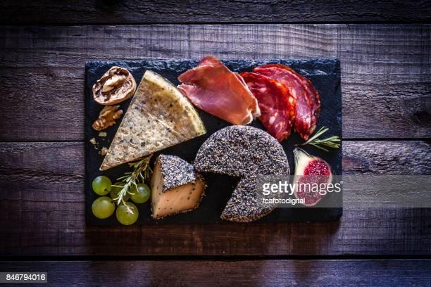 Tablero de carne queso y frío en la rústica mesa de madera