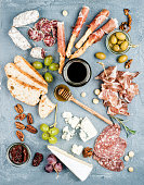 Cheese and meat appetizer selection or wine snack set. Variety of  cheese, salami, prosciutto, bread sticks, baguette, honey, grapes, olives, sun-dried tomatoes and pecan nuts over grey concrete textu