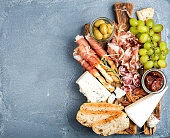 Cheese and meat appetizer selection. Prosciutto di Parma, salami, bread sticks, baguette slices, olives, sun-dried tomatoes, grapes and nuts on rustic wooden board over grey concrete textured backdrop