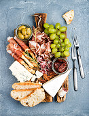 Cheese and meat appetizer selection. Prosciutto di Parma, salami, bread sticks, baguette slices, olives, sun-dried tomatoes, grapes and nutson rustic wooden board over grey concrete textured backdrop,