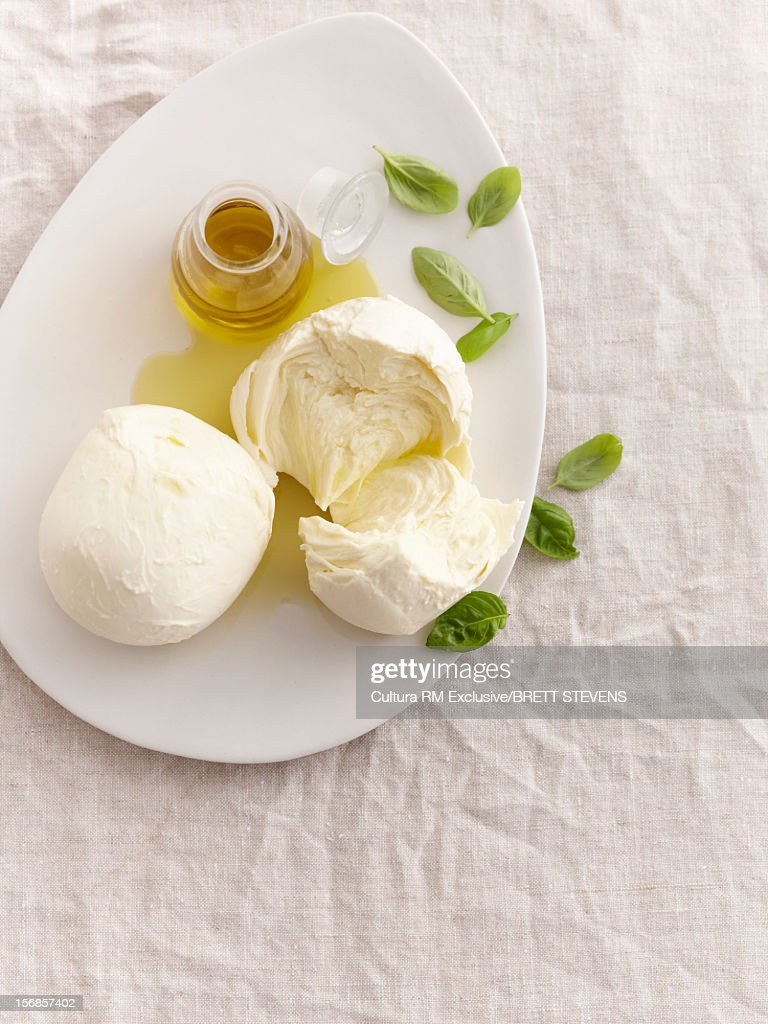 Cheese balls with oil and basil leaves : Stock Photo