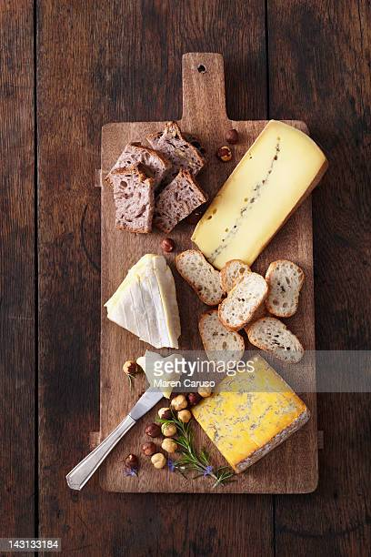 Cheese, bread, and nuts served on cutting board
