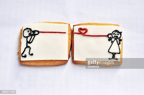 Cheese cracker with drawings of a girl talking to a boy using tin can telephone