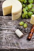 Cheese, grapes, cork and corkscrew on an old wooden table.