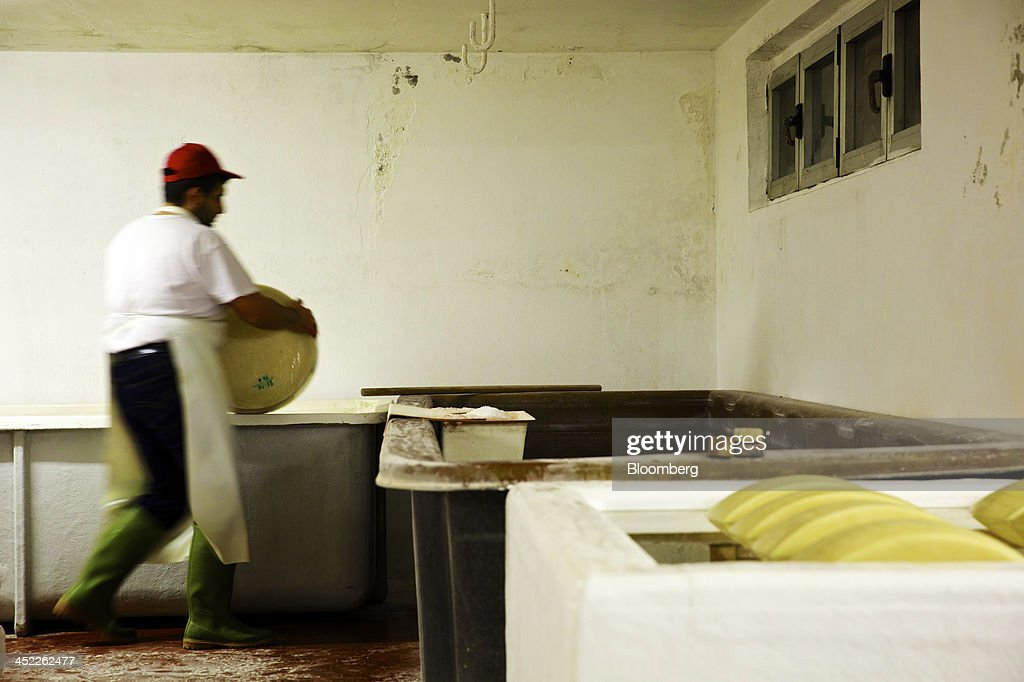 A cheese maker checks the progress of a whole cheese during the salting process of Parmigiano Reggiano manufacturing at Il Trionfo cheese makers in San Secondo Parmense, Italy, on Tuesday, Nov. 26, 2013. Italian borrowing costs dropped at an auction of six-month bills as investors await signals from the European Central Bank about further stimulus. Photographer: Gianluca Colla/Bloomberg via Getty Images