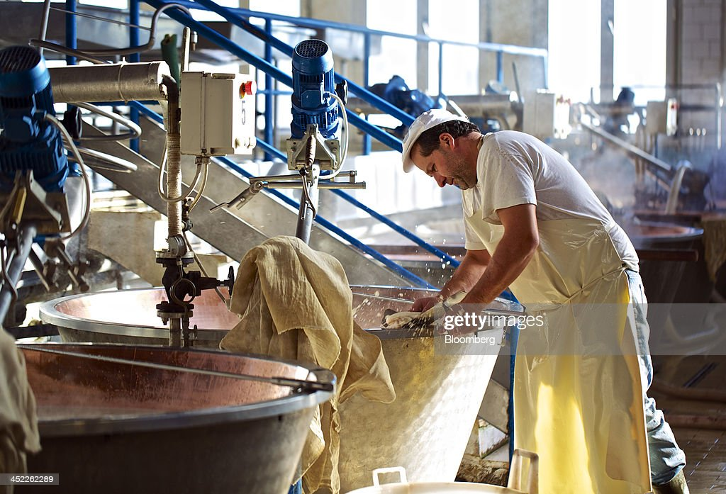A cheese maker cleans a copper cauldron used in the Parmigiano Reggiano cheese manufacturing process at Il Trionfo cheese makers in San Secondo Parmense, Italy, on Tuesday, Nov. 26, 2013. Italian borrowing costs dropped at an auction of six-month bills as investors await signals from the European Central Bank about further stimulus. Photographer: Gianluca Colla/Bloomberg via Getty Images