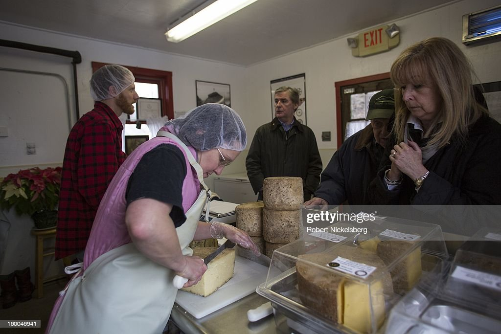 Cheese maker Heather Shepheard, second left, cuts a piece of aged cheese for a customer January 11, 2013 at the Cato Corner Farm in Colchester, Connecticut. The Cato Corner Farm has been making artisanal cheese from raw milk for over 15 years. The cheese is sold to restaurants and at farmer's markets in the New York City area. The farm is owned and operated by a mother and son team, Elizabeth McAlister and Mark Gillman.