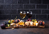 Cheese plate with grapes, figs, dips and wine. Selective focus